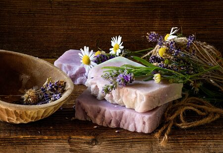 Handmade Soap with lavender and chamomile flowers on rustic wooden table.