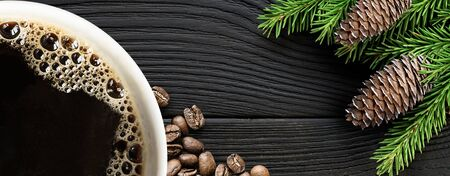 Coffee cup with coffee beans and christmas tree branch on black wooden background