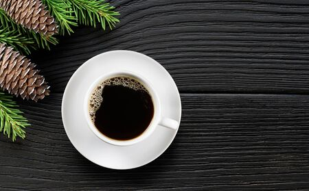 White Coffee cup and christmas tree branch with cones on black wooden background