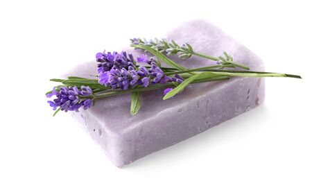 Homemade lavender soap bar with lavender flowers atop isolated on white.