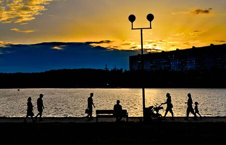 People walking along the shore of the pond in residential area at sunset.