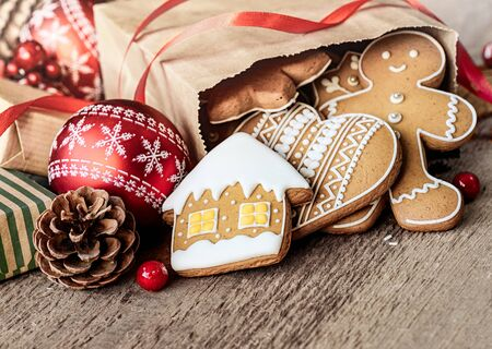 Christmas cookies in paper bag on wooden table Фото со стока