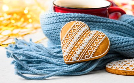 Gingerbread heart and red mug wrapped in blue scarf Фото со стока