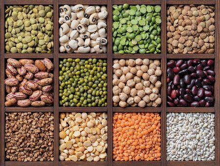 Legumes and cereal bood background : lentils haricot beans chickpea pea in wooden box close-up Фото со стока