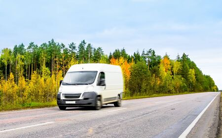 Van fast moving on asphalt road in the countryside on autumn landscape background. Small truck delivers the goods