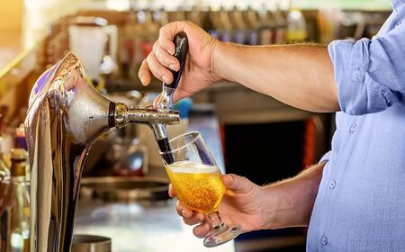 Barman pours the beer into a glass from the tap. Imagens