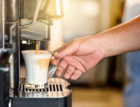 Hand taking coffee cup in automated coffee making machine. Imagens