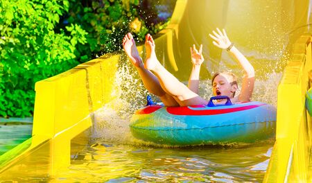 Boy having fun on yellow water slide at water park