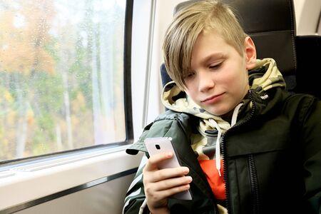 Teenage boy using his smartphone sitting near the window in train.