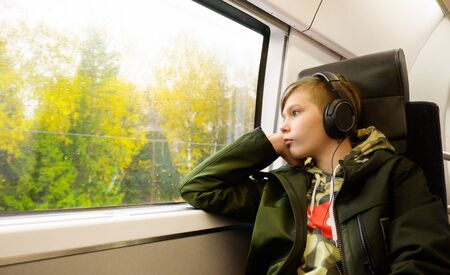 Teenage boy listen music with headphone while traveling by train