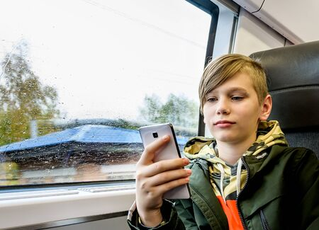 Teenager boy using his smartphone while traveling by train