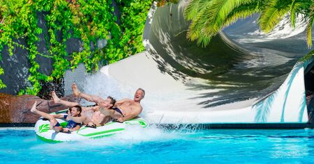 Family having fun on water slide at water park. Summer holiday.