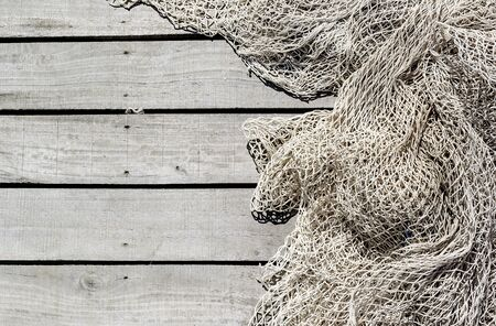 Fishing net on wooden decking background Imagens