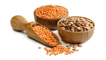 Lentils in a wooden bowls and scoop isolated on white background. Full depth of field Stock Photo