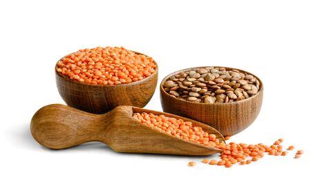 Brown and red lentils in a wooden bowls and scoop isolated on white background.