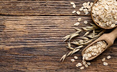 Oat flakes in the bowl with Wooden scoop and oat plant on old rustic plank wooden background. Top view copy space Imagens