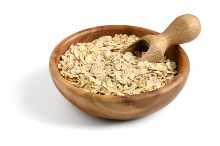 Oat flakes with wooden scoop in wooden bowl isolated on white.