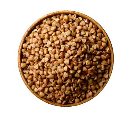 Dry food buckwheat grains in wooden bowl isolated on white.