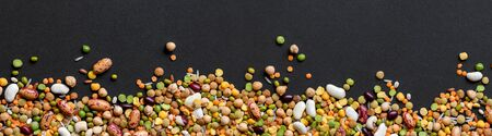 Colorful mixed cereals and legumes on black background. Wide panoramic view.