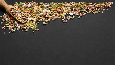 Colorful mixed legumes and cereals with wooden scoope on black background. 版權商用圖片 - 133782490