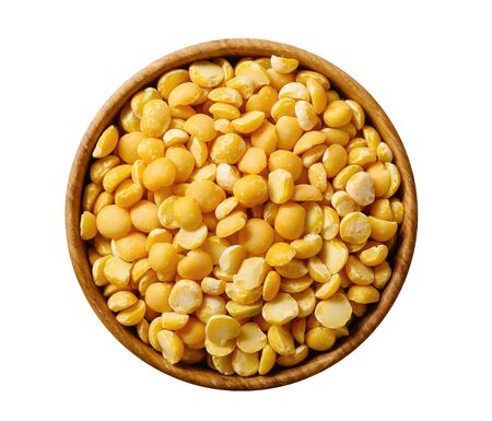 Dried splin yellow peas in wooden bowl isolated on white