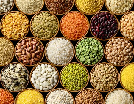 Various colorful legumes and cereals on black background