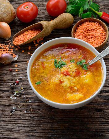 Red lentil soup on the rustic wooden table. Vertical image