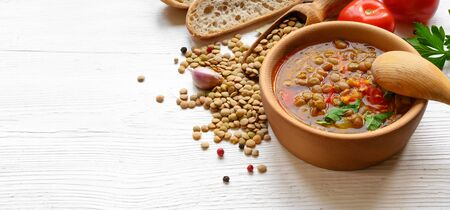 Lentil soup with tomatoes in wooden bowl on white table