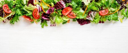 Mixed fresh lettuce and vegetables on a white wooden table. Background, border, frame, site title 版權商用圖片 - 133782603