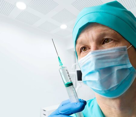 Doctor in mask and glove holding medical syringe.