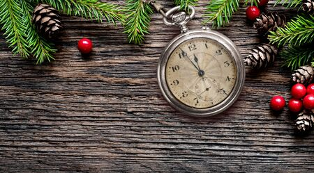 New Year old pocket watch eve to midnight with fir branches background