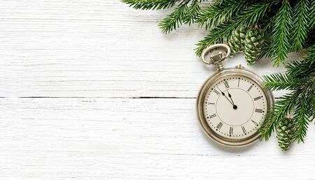 New Year old pocket watch eve to midnight with fir branches and green cones. Фото со стока