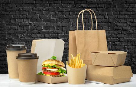 Fast food big lunch packaging set on black brick wall background.