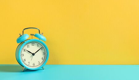 Turquoise vintage alarm clock on yellow background.