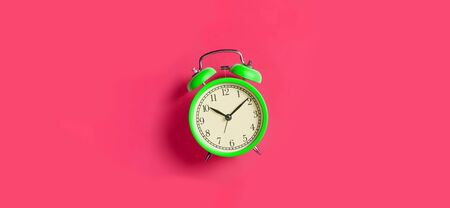 Green vintage alarm clock on bright fuchsia red background. Top view, flat lay, copy space