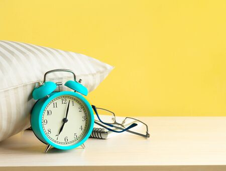 Alarm clock near the pillow on the bedside table. Copy space.