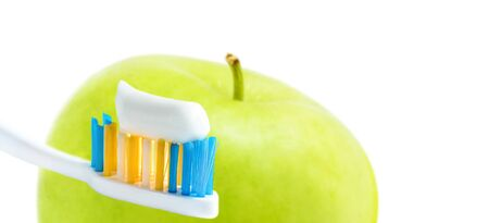 Toothbrush with squeezed paste close-up and green apple isolated on white. Dental care concept. Shallow DOF, selective focus.
