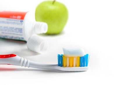 Toothbrush with squeezed paste, tube of toothpaste and green apple on white background. Selective focus.