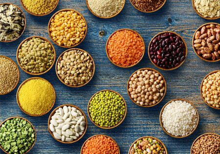 Cereals and legumes in wooden bowls on old wooden background. Food theme background. Flat lay Фото со стока