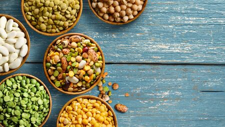 Legumes in wooden bowls on old blue wooden table. Flat lay. Copy space. Stock Photo