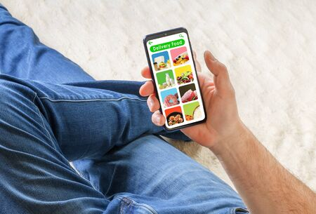 Man in casual wear lying on sofa and holding phone with app delivery food on screen.
