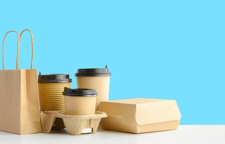 Assortment of food delivery containers on the table. Paper coffee cups in holder, food box, brown paper bag. Foto de archivo