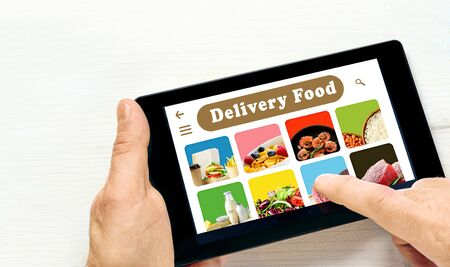 Men's hand holding tablet computer with app delivery food on screen above white desk.