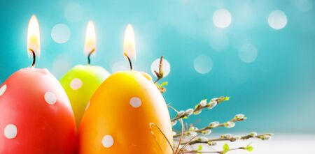 Easter colorful candle eggs with willow twigs on blurred blue background with bokeh lights. Copy space. Soft focus Banco de Imagens
