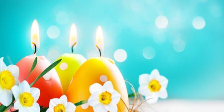 Easter colorful candle eggs with daffodils flowers on blurred blue background with bokeh lights. Copy space. Soft focus Banco de Imagens