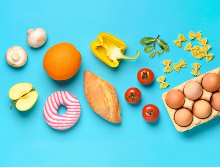 Online food Grocery shop background. Different healthy food products on a blue background. Top view. Flat lay.