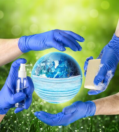 Protection against global coronavirus infection concept. Earth planet in medical protective mask on green nature background. Save the planet.