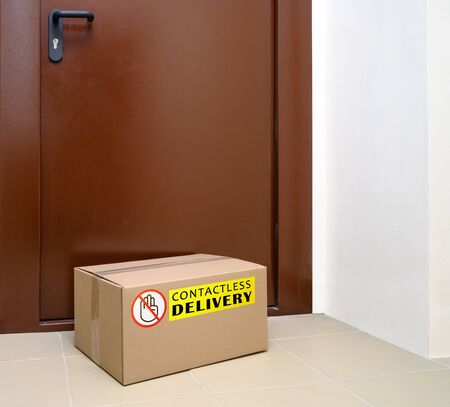 Contactless delivery left at the door during the quarantine. Apartment entrance with delivered box. Control Epidemic Prevention measures of coronavirus.