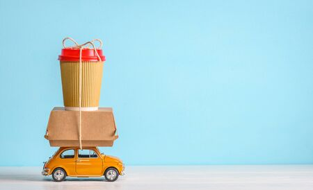 Retro toy car delivering food order on blue background. Copy space