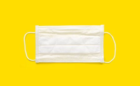Medical face mask on yellow background. Protection against coronavirus, flu and other airborne infection. Copy space, directly above. Banco de Imagens